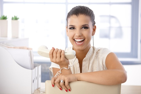 Attractive young girl laughing in office, with receiver in hand. photo