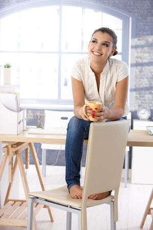 fantasize: Attractive young girl daydreaming, sitting on top of desk, drinking tea.