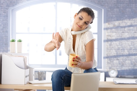 Young girl sitting in office, talking on landline phone, looking at nails, drinking tea. Stock Photo - 10377684