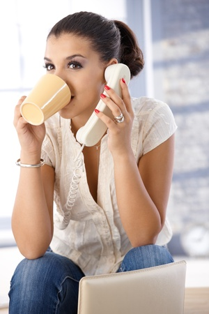 Pretty girl talking on phone, drinking tea. Stock Photo - 10377673