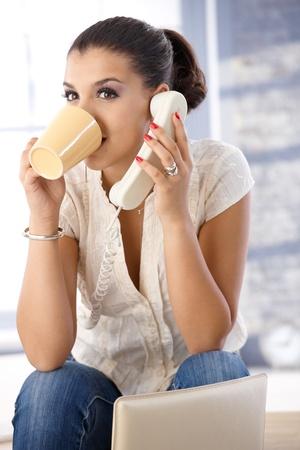 Pretty girl talking on phone, drinking tea. Stock Photo - 10377673