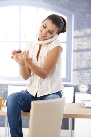 Happy girl talking on phone, filing nails in bright office. Stock Photo - 10377665