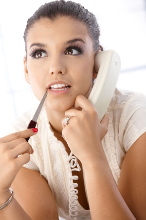 Portrait of beautiful young woman talking on phone. Stock Photo - 10377602