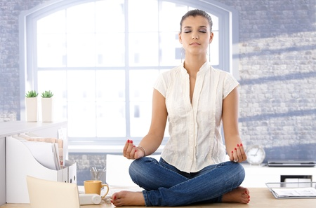offish: Pretty girl sitting on top of desk in bright office, meditating.