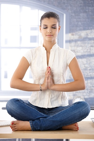 offish: Young attractive female sitting on top of desk, meditating.
