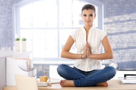 Attractive young woman relaxing in bright office, meditating. photo