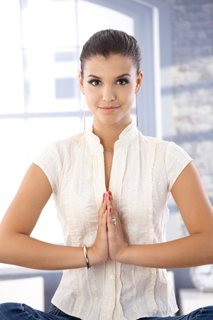 offish: Attractive young girl meditating, smiling. Stock Photo