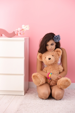 kneeling woman: Pretty teenage girl kneeling on floor, hugging teddy bear in pink room.
