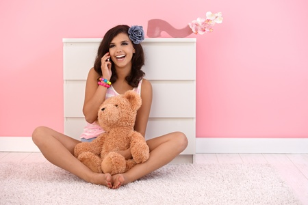 seventeen: Beautiful girl sitting on floor with teddy bear, talking on mobile phone.