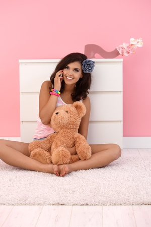 poner atencion: Joven charlar en móviles, sonriente, sentado en el piso de su habitación rosa con osito de peluche.