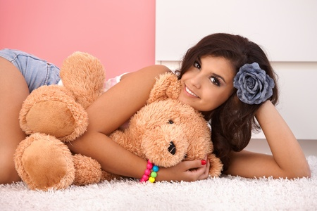 only teenage girls: Sexy girl laying on floor, hugging teddy bear, smiling.