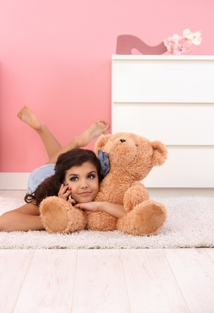 soft toy: Pretty girl laying on floor, hugging huge soft toy bear, talking on mobile phone. Stock Photo