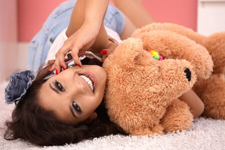lay: Beautiful girl on mobile phone, laying on floor hugging teddy bear. Stock Photo