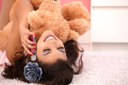 Attractive girl laying on floor at home, hugging huge teddy bear, chatting on mobile. Stock Photo - 10377633