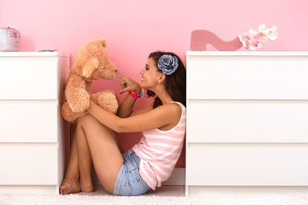 soft toy: Pretty teenage girl playing with toy bear in her room.