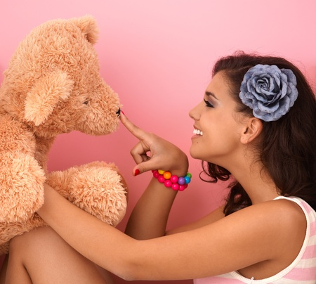 Young girl playing with big teddy bear at home. photo