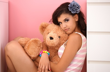 only teenagers: beautiful teenage girl hugging teddy bear, looking at camera. Stock Photo