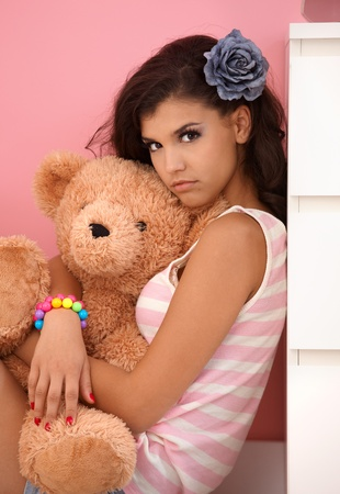 unsmiling: Attractive young girl hugging toy bear, looking at camera.