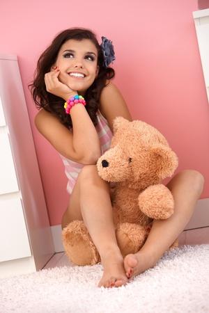 one teenage girl only: Feliz adolescente sentado en el piso en casa con el oso de peluche, sonriente, so�ando despierto.