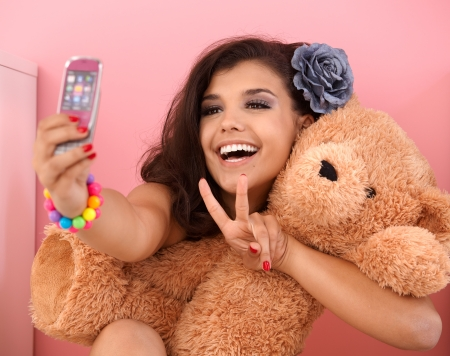 Pretty girl photographing herself and toy bear by mobile phone, smiling. photo