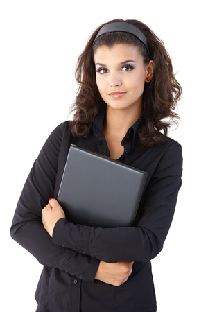 Pretty young businesswoman holding laptop, looking at camera. photo