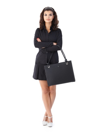 short skirt: Confident young businesswoman standing arms crossed, looking at camera.