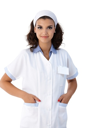 hand in pocket: Portrait of pretty young nurse in lab coat, smiling. Stock Photo