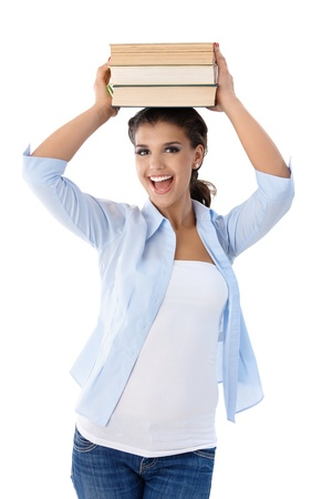Beautiful college student holding books on top of head, smiling happily, looking at camera. photo