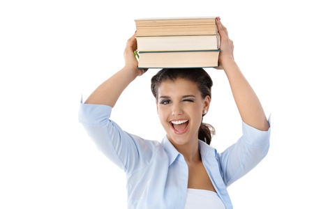Pretty young girl holding books on her head, winking, smiling. photo