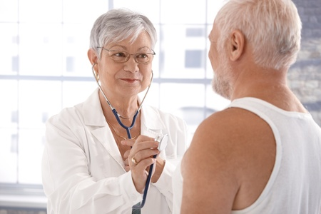 exam room: Senior female doctor examining patient, using stethoscope. Stock Photo