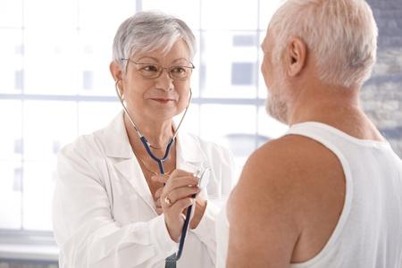 image consultant: Senior female doctor examining patient, using stethoscope. Stock Photo