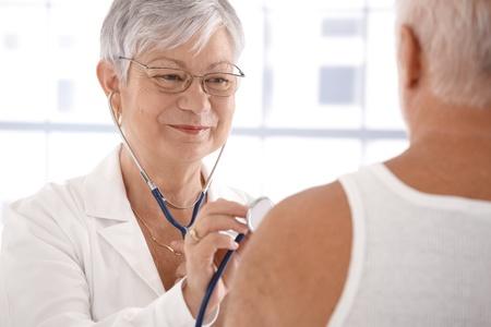 mujeres ancianas: Senior femenino m�dico examinador paciente masculino, sonriendo.