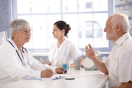 Senior patient sitting at doctors room, consulting with female doctor. photo