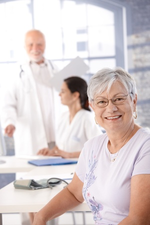 consulting room: Elderly lady sitting at doctors room, waiting for health control, smiling.