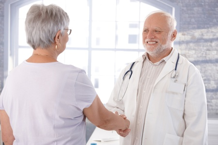 Senior doctor and female patient shaking hands, smiling.
