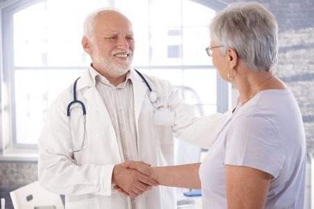 Mature male doctor and senior female patient shaking hands, smiling. photo