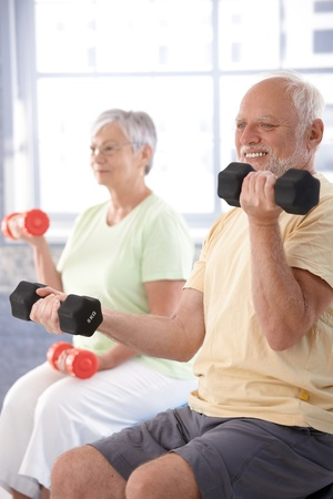 Elderly man exercising with dumbbells at gym.