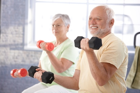 female senior adults: Senior people doing dumbbell exercises in the gym. Stock Photo