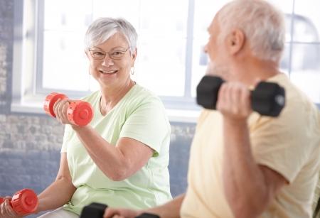 Vital senior couple exercising in the gym. photo