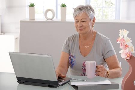 Elderly woman working on laptop computer, smiling, drinking tea.