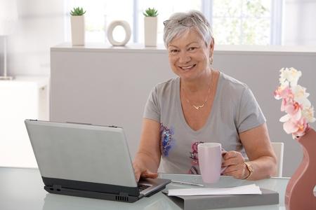 one senior adult woman: Senior mujer trabajando en equipo port�til, mirando la c�mara, beber t�.