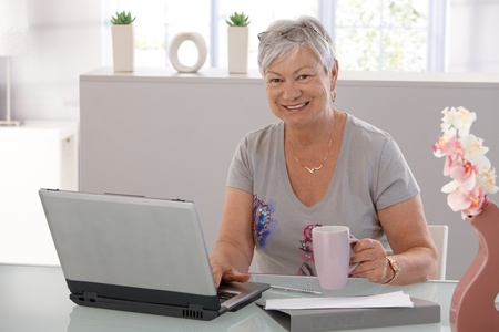 only senior adults: Senior woman working on laptop computer, looking at camera, drinking tea.