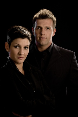 good looking woman: Portrait of young business couple in black, isolated on black background.