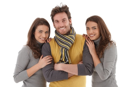 Beautiful female twins embracing handsome young man, all smiling at camera.