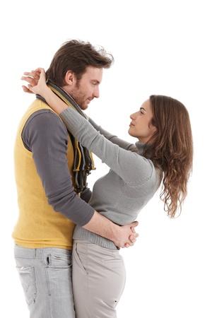 tenderly: Moda giovane coppia che abbraccia teneramente, baciare, vista laterale.