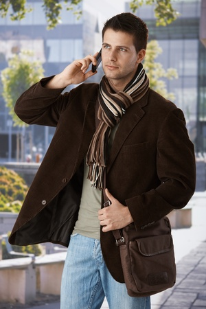 Goodlooking man on mobile phone call standing outside of office building in spring sun, wearing trendy bag and scarf. photo