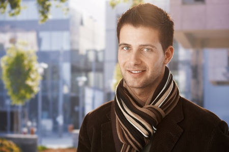 1 man only: Outdoors portrait of handsome guy standing outside of office building, wearing scarf.