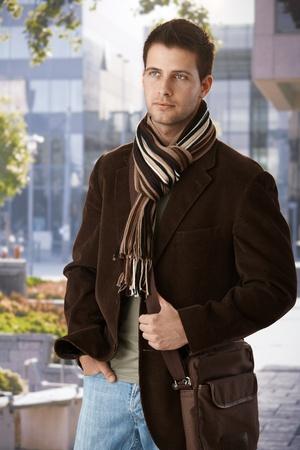 shawl: Knappe man in trendy kleding met sjaal en tas stond op te wachten buiten het gebouw. Stockfoto