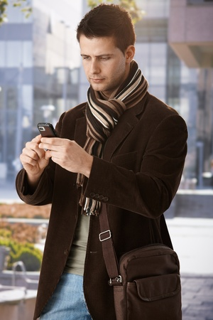 Trendy guy texting on mobile phone, standing outside of building in sun. Stock Photo - 10427482