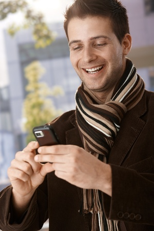 Happy guy wearing scarf looking at mobile phone handheld, laughing. photo